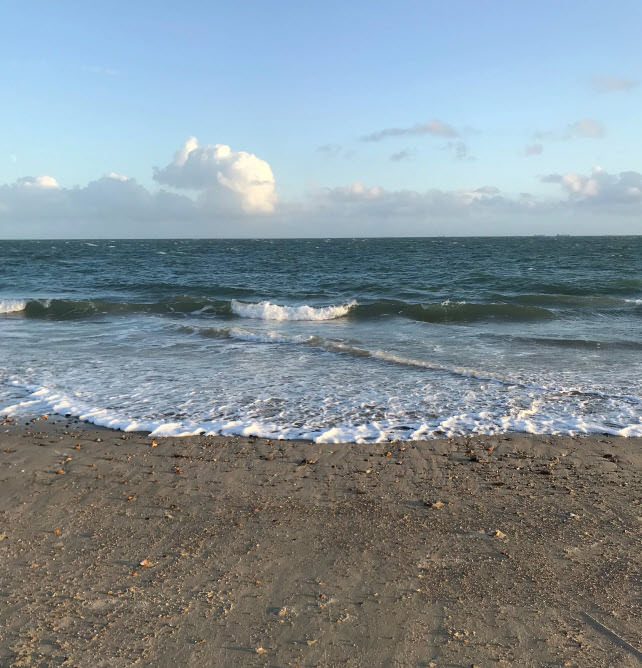 A sandy beach with the sea rolling in and slopping away. With a few clouds on the horizon of a clear blue sky.